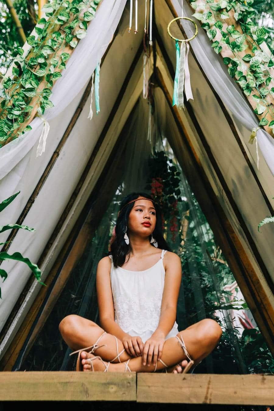 woman in white sleeveless dress sitting on bamboo tree 3431567